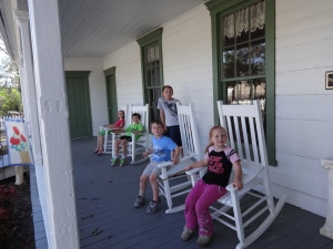 Sitting on the cute front porch of the historical building.